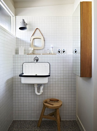 A tiled bathroom has an industrial feel.