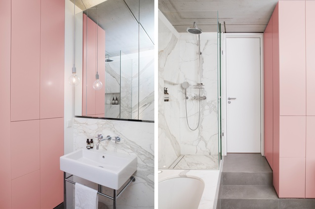 The black box of the bathroom's external walls hides a soft pink and marble room inside.