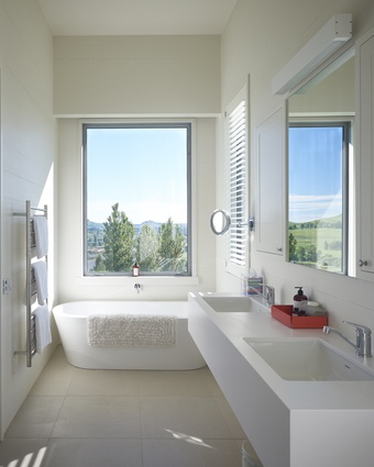 In the master suite, a freestanding bath offers a view of the pony club.