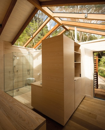 Glazing over the bathroom creates a light-filled space with a view of the sky and the treetops. Through the doorway is an external shower.