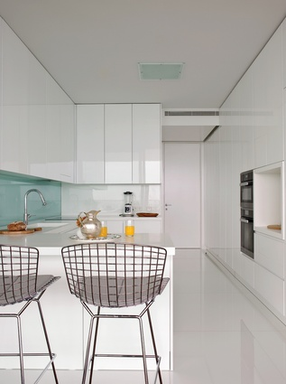 The kitchen receives ample sunlight, which reflects off the glossy white surfaces and Harry Bertoia barstools.