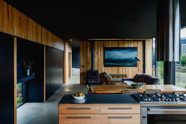 Black ceilings and cabinetry lend contrast and definition to the raw-material palette of timbers and untreated metals in the kitchen.