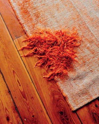 "Vintage rug: ""This is an old, worn-down Turkish rug that has been re-dyed in bright orange. We purchased it like that from a great shop called Loom Rugs""."