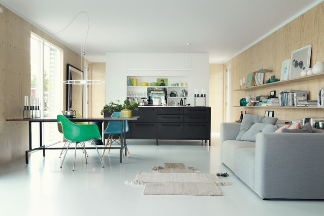 The main living area is anchored by a Vipp kitchen. Eames chairs, Hay sofa and a Titania light from Luceplan are in keeping with the Scandinavian aesthetic.