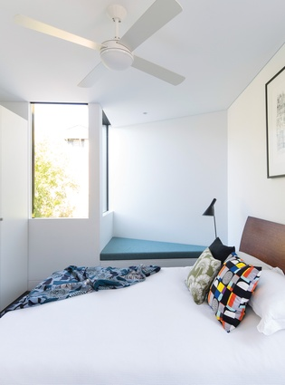 A window seat juts out from the main bedroom on the upper level, contributing to the external form of the extension.