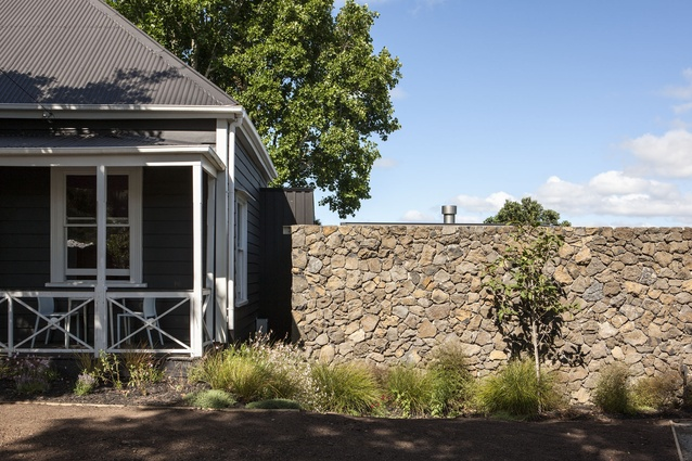 A scoria wall creates a strong contrast beside the old bungalow at the front of the property.