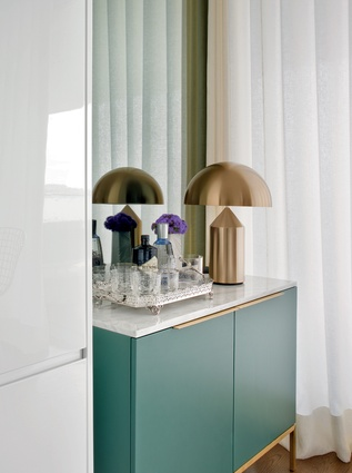 The small bar area in the kitchen, adorned with a Vico Magistretti lamp, features brass detailing and a mint-coloured finish to contrast with the room's white, glossy surfaces.