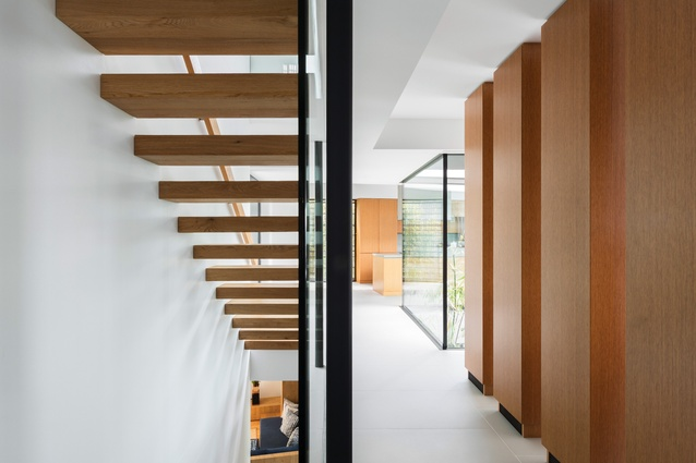Cantilevered timber stairs to the upper and lower levels are shielded from the living area by a series of timber box forms that are storage cupboards and service risers.