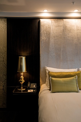 A suite with a velvet headrest, golden fabrics and light-coloured shelves.