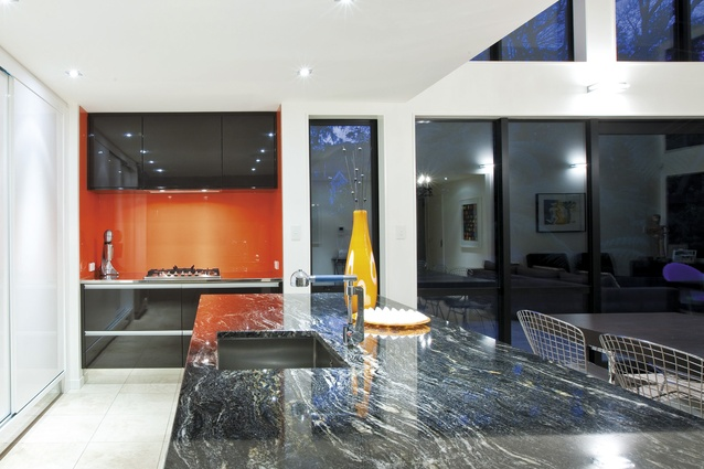 Natalie Du Bois designed the orange kitchen. The zingy orange in the kitchen splashback was inspired by one of the clients' artworks displayed in the adjoining living area. As a surprise, when the white cupboards are opened, the orange is also the backdrop to the shelving.