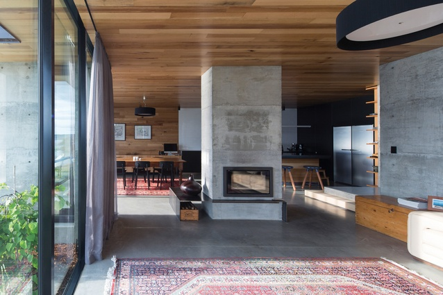 The L-shaped living space consists of three zones – kitchen, dining and sitting – with a central fireplace.