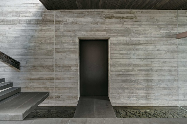 One of the large concrete walls sits behind a narrow tributary running through the space.