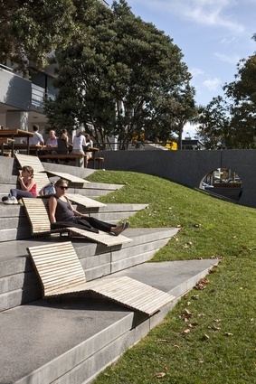 Bleachers with lounge furniture and interesting triangular insertion into mound of earth.