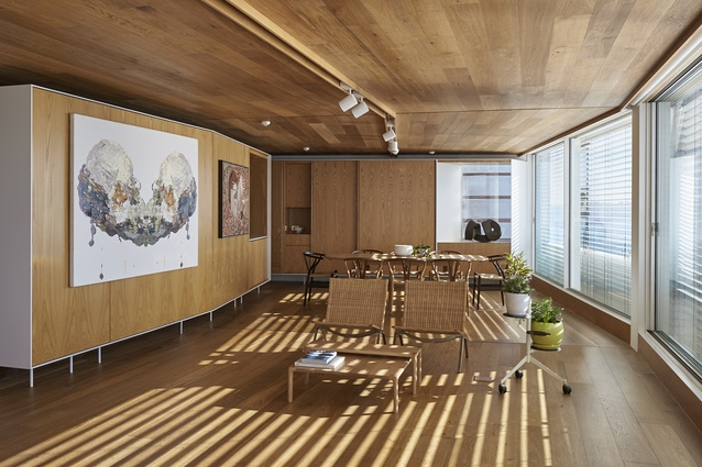A lighting track follows the kinking geometry of the room, with the floorboards and ceiling emphasising the bending of the space to give a sense of elongation.