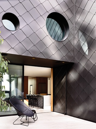 Dark zinc shingles contrast with a light-filled interior at an Asian-influenced Melbourne residence.