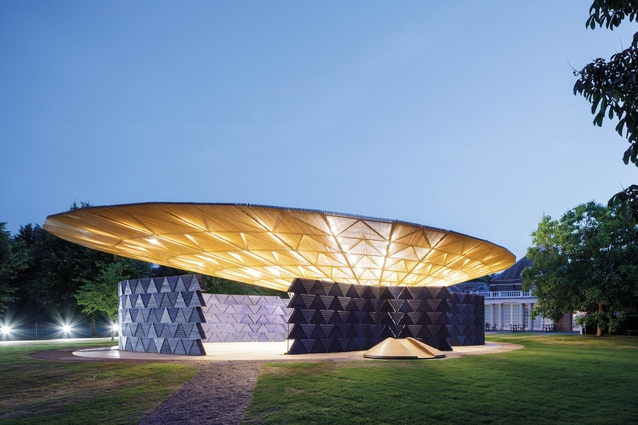 This night-time shot shows the roof illuminated. Around the pavilion's perimeter, circular timber slides keep children entertained.