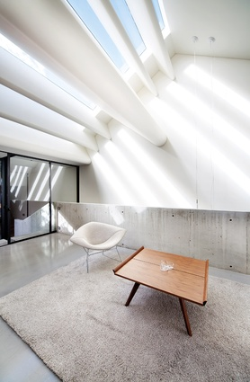 Glass bands are separated by sculpted white blades over the living room, infusing it with shafts of light.