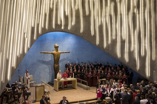 Cathedral of the Northern Lights, 2013. Daylight enters the interior through narrow, irregularly placed windows, with a skylight lighting up the entire wall behind the altar.