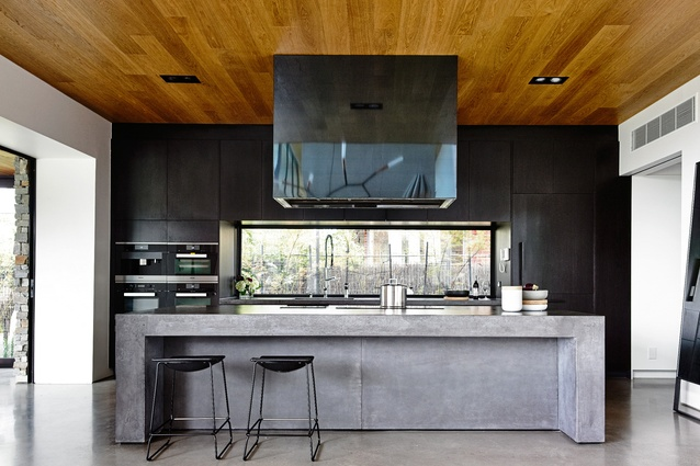 The sleek black kitchen has a lower ceiling than the living space; almost every transition from one space to another is marked by a change in ceiling height.