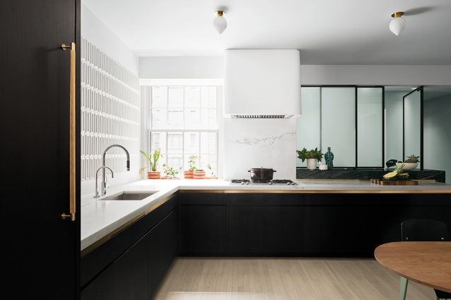 White marble countertops complement the kitchen's lacquered and ebonised oak pantry.