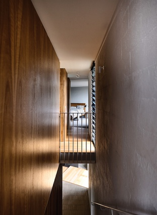 A stairwell along the western edge leads from the entryway to the living spaces and main bedroom on the upper level.