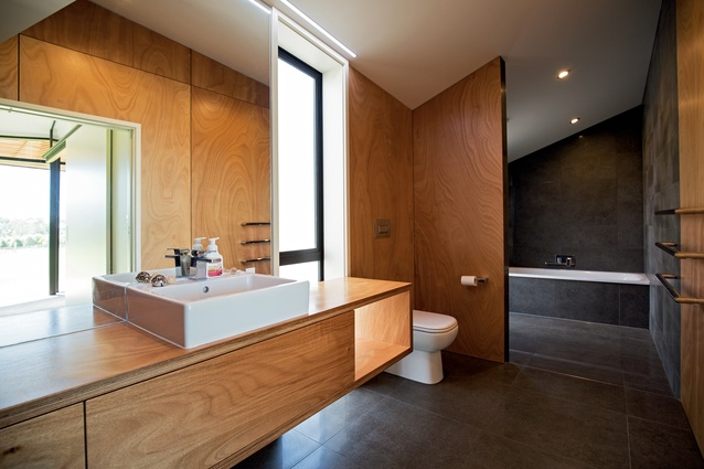 The bathroom features a large wet area combining the shower and bath. Gaboon plywood was also used extensively in this space.