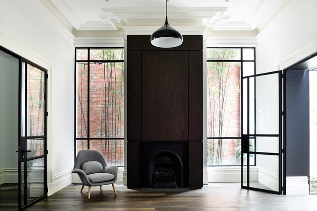 The existing fireplace is wrapped by dark veneer joinery panels, referencing proportions typical of late-nineteenth-century residential architecture.
