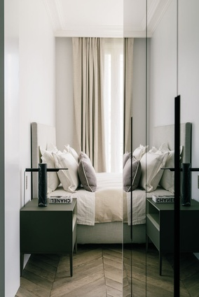 The parquet flooring in the bedroom lends the space a warm, rustic aesthetic.