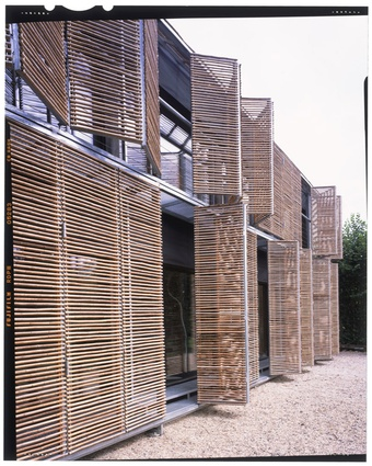 Passive House, France. The outer shell is entirely covered with cut-to-measure bamboo poles threaded onto steel wires, which creates a filigree effect.