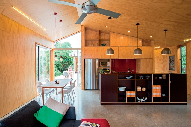 Werry House, built 2015. The U-shaped plan wraps around a central courtyard. The kitchen and dining area showcases Bonnifait + Giesen's signature plywood-lined interiors.