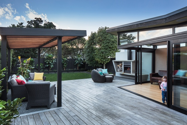 The living room flows seamlessly into the rear courtyard with stacked sliding doors.