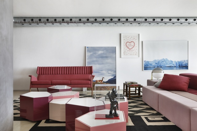 A seeming mismatch of objects, art and furniture is grounded by tones of pink.