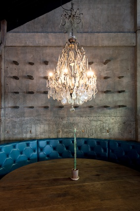 Antique glove moulds line the walls of the round banquette booth.