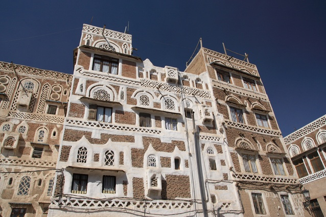 Hand-cut stone buildings in Sana'a, Yemen. These medieval-like towers have high thermal mass and small windows to keep occupants cool. Traditional construction using ancient methods and materials is still widespread in Yemen.