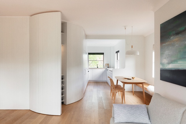 The insertion of a curved timber-panelled joinery wall defines the zones within the apartment, conceals original splayed walls and provides storage space.