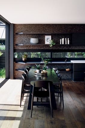 The kitchen and living room furniture is chosen to match the tones of the tiled wall. The kitchen table was custom made by Mckean Carnell, while the chairs were sourced from Backhouse.