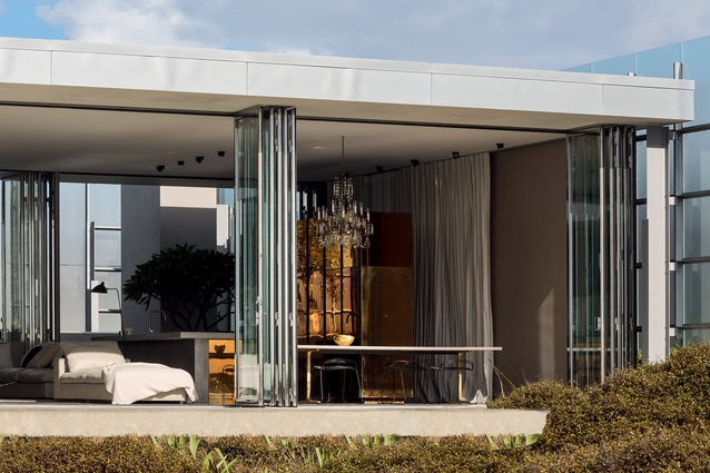 The house is designed to provide both protection and outlook, with spaces opening to a translucent glass screened courtyard to the south and a terrace overlooking the sand dunes and beach to the north.