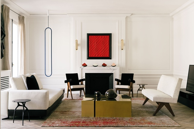 The lounge room features contemporary artworks alongside classic design pieces in a subdued colour palette.