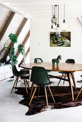 "Dining table by Lowe. ""A round dining table is convivial and works well in this square space. It's big and inviting."""