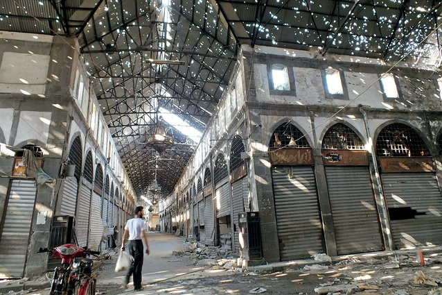 A civilian wanders the bullet-holed roof of the historic Souk Maskouf market in Old Homs in 2013 after Syrian forces took over much of the city which had been held by the so-called rebels, ending a two-year seige.